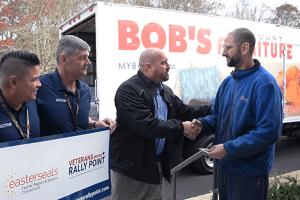 A representative from Bob's Discount Furniture presents a veteran with a gift card.