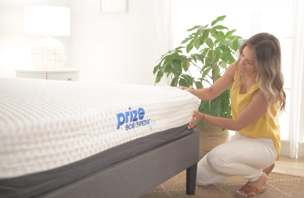 Carolina adjusts the corners of the mattress | Bob's Discount Furniture
