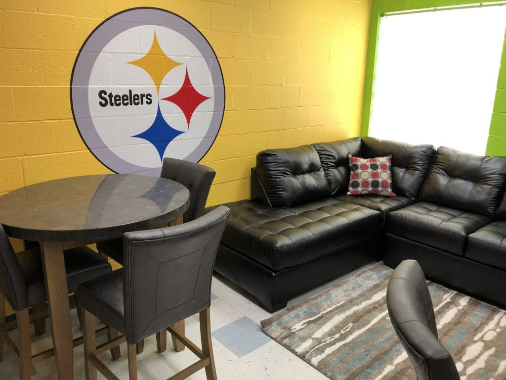 The music studio featured a Steelers logo flanked by a Mercury Onyx sectional and Montibello Bluestone table | Bob's Discount Furniture