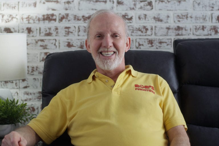 Bob Kaufman, the founder of Bob's Discount Furniture, sits on a sofa.